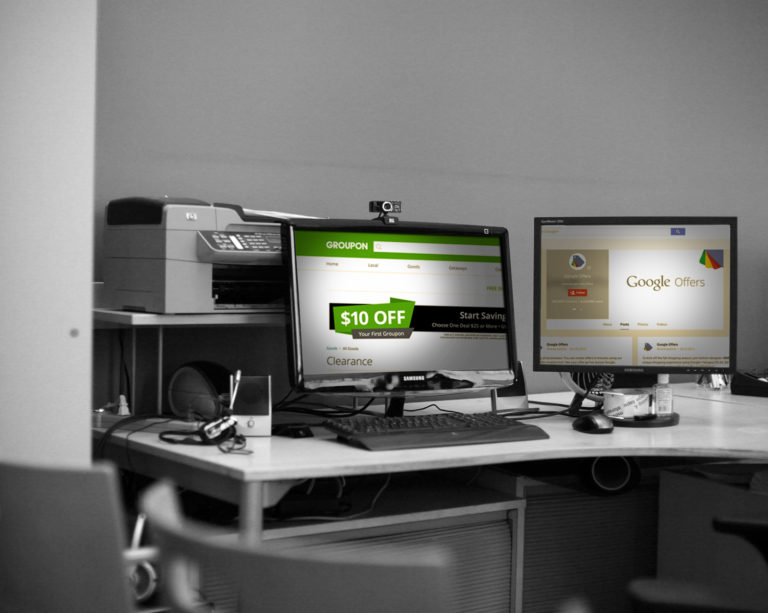 two monitors open to groupon and google offers